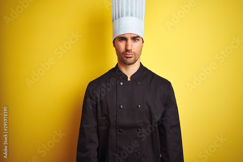 Pinturas sobre lienzo  Young chef man wearing uniform and hat standing over isolated yellow background skeptic and nervous, frowning upset because of problem