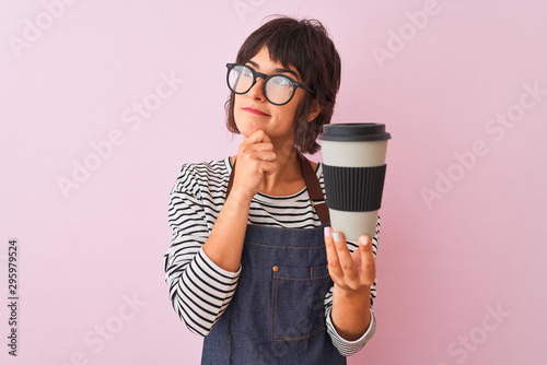 Young beautiful barista woman wearing glasses holding coffee over isolated pink background serious face thinking about question, very confused idea - 295979524