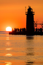 Lighthouse At Sunset With Silhouette People