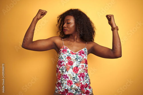 Canvastavla  African american woman wearing floral summer t-shirt over isolated yellow background showing arms muscles smiling proud