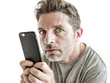 freak and weird looking man using mobile phone watching something online in sick intense face expression in internet and social media addiction concept isolated