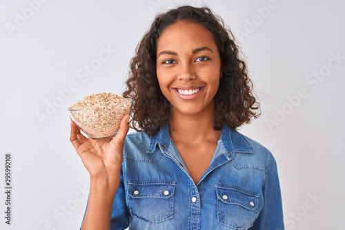 Young brazilian woman holding oat bowl standing over isolated white background w Fototapet