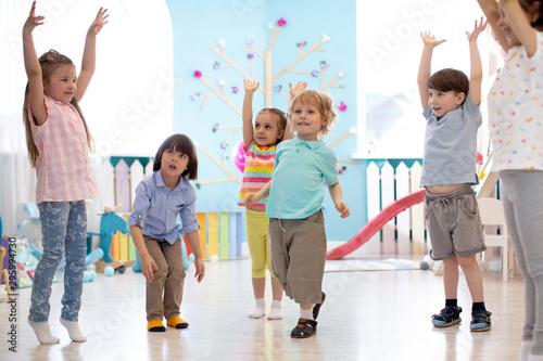 Group of preschool children doing gymnastics in kindergarten Fototapet