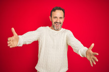 Handsome Middle Age Senior Man With Grey Hair Over Isolated Red Background Looking At The Camera Smiling With Open Arms For Hug. Cheerful Expression Embracing Happiness.