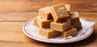 Caramel fudge candies on a plate. Wooden background. Close up.