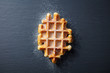canvas print picture - Belgian waffle with icing sugar. Slate background. Top view.