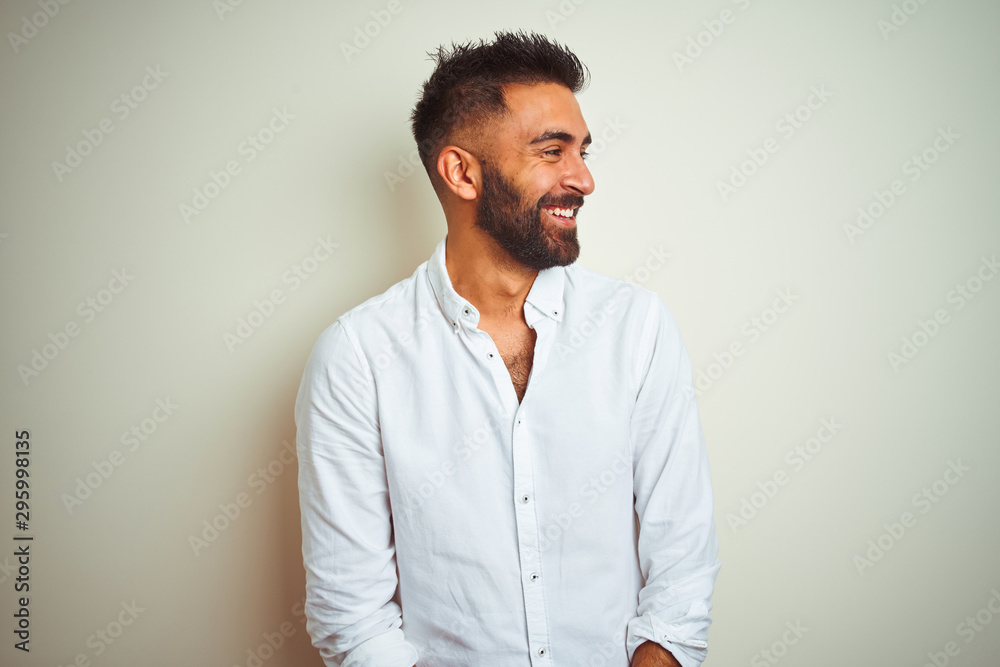 Fototapeta Young indian man wearing elegant shirt standing over isolated white background looking away to side with smile on face, natural expression. Laughing confident.