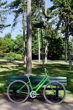 Vertical Shot Of A Green Bicycle Leaned Against A Wooden Bench In A Park At Daytime