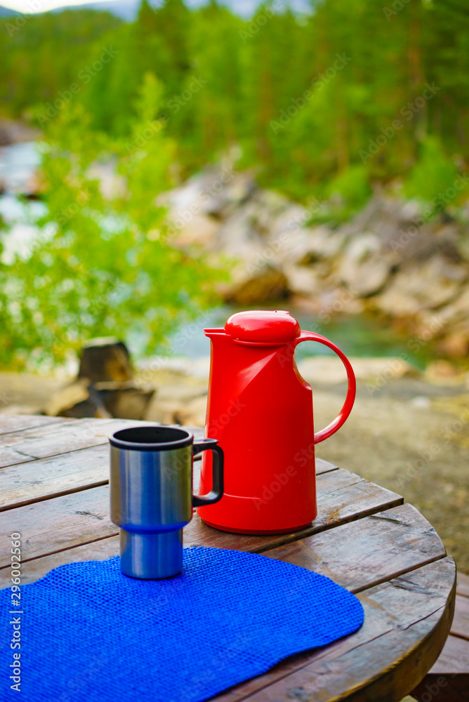 Fototapety, obrazy: Picnic site table with thermos and thermal mug, norwegian mountains nature in the background. Camping with thermos.