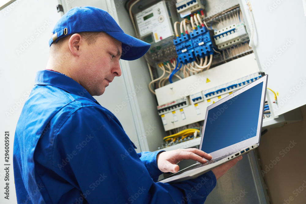 Fototapety, obrazy: Electrician works with computer laptop near switchbox