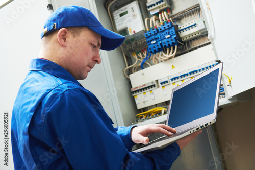 Photo  Electrician works with computer laptop near switchbox