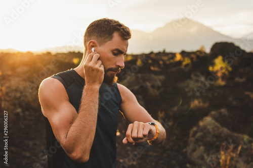 Photo Male runner synchronizing wireless earphones with smart watch