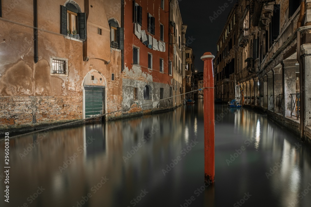 Horizontal shot of a canal between the old buildings in Venice, Italy during nighttime