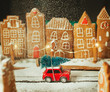 canvas print picture - Toy car with Christmas tree in the gingerbread town during sugar snowfall