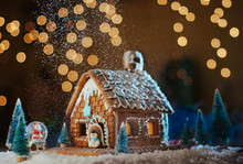 Traditional Christmas Gingerbread House With Snowfall On Garland Lights Background
