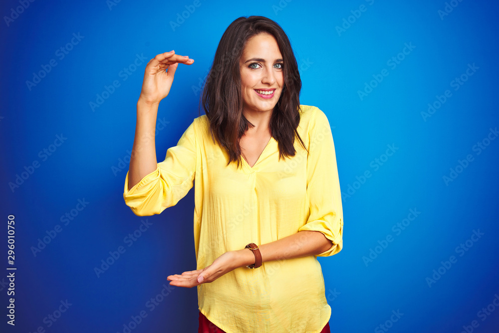 Obraz Young beautiful woman wearing yellow t-shirt standing over blue isolated background gesturing with hands showing big and large size sign, measure symbol. Smiling looking at the camera fototapeta, plakat