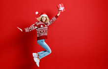 Happy Young Cheerful Girl Laughs And Jumps In Christmas Hat And With  Gift On  Red   Background