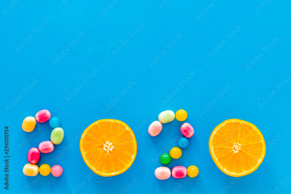 Fototapety, obrazy: Sweet New Year design. 2020 laid out with candy and oranges on blue background top view copy space