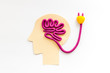 Brain charging and mental rest. Plug and cable leads to plastiline meanders on white background top view