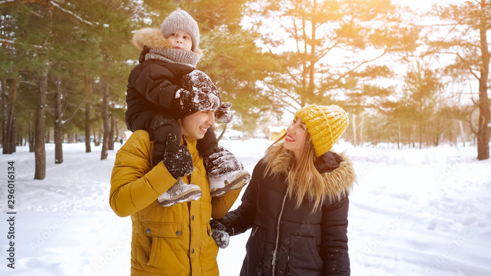 Fototapety, obrazy: Happy young family, mom, son and dad are walking together in winter park, copyspace. Woman is showing something by her hand to her husband and son.