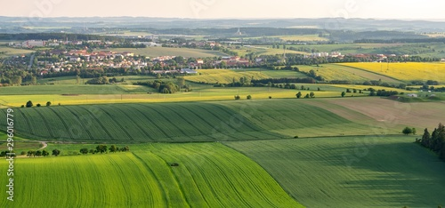 Breathtaking aerial shot of green fields on hills next to small settlement