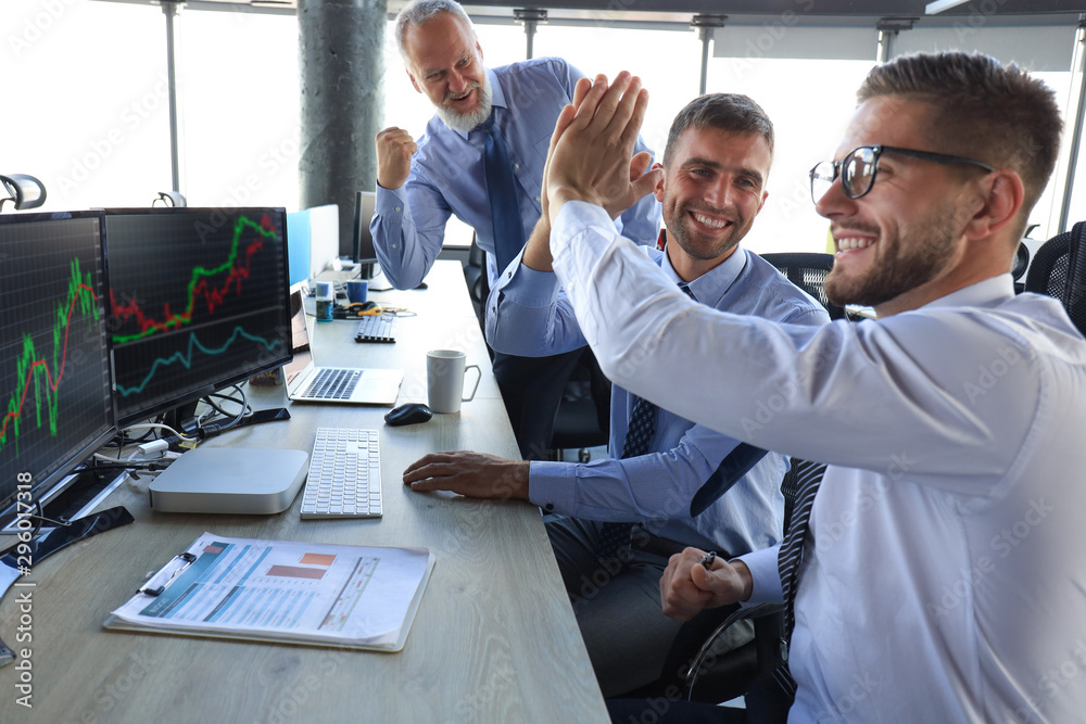 Fototapeta Group of modern business men in formalwear smiling and gesturing while working in the office.