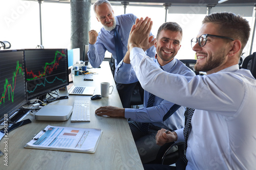 Fotomural  Group of modern business men in formalwear smiling and gesturing while working in the office