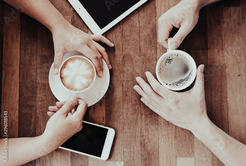 Wall Murals Cafe Couple hand holding hot coffee cup on wooden table.Business man and woman drinking espresso and latte art menu with tablet and mobile phone in the restaurant.Lover in coffee shop.