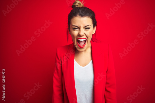 Fotografía  Young beautiful business woman standing over red isolated background angry and mad screaming frustrated and furious, shouting with anger