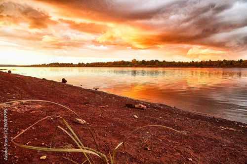 Photo sur Toile Rouge mauve Sky with fantastic, amazing, stormy, disturbing red clouds over the river on a summer or autumn evening