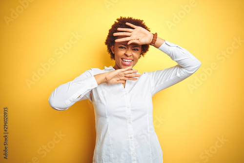 Valokuva  African american business woman over isolated yellow background Smiling cheerful playing peek a boo with hands showing face
