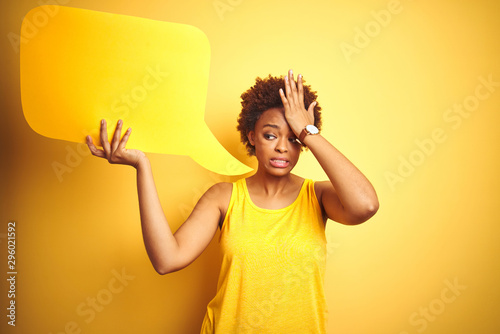 Fotomural  Young african american woman holding speech bubble over yellow isolated background stressed with hand on head, shocked with shame and surprise face, angry and frustrated