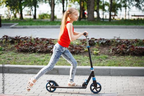 Fototapeta Teen Child riding a scooter in a city park. obraz