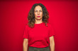 Leinwanddruck Bild - Middle age senior woman with curly hair over red isolated background with serious expression on face. Simple and natural looking at the camera.