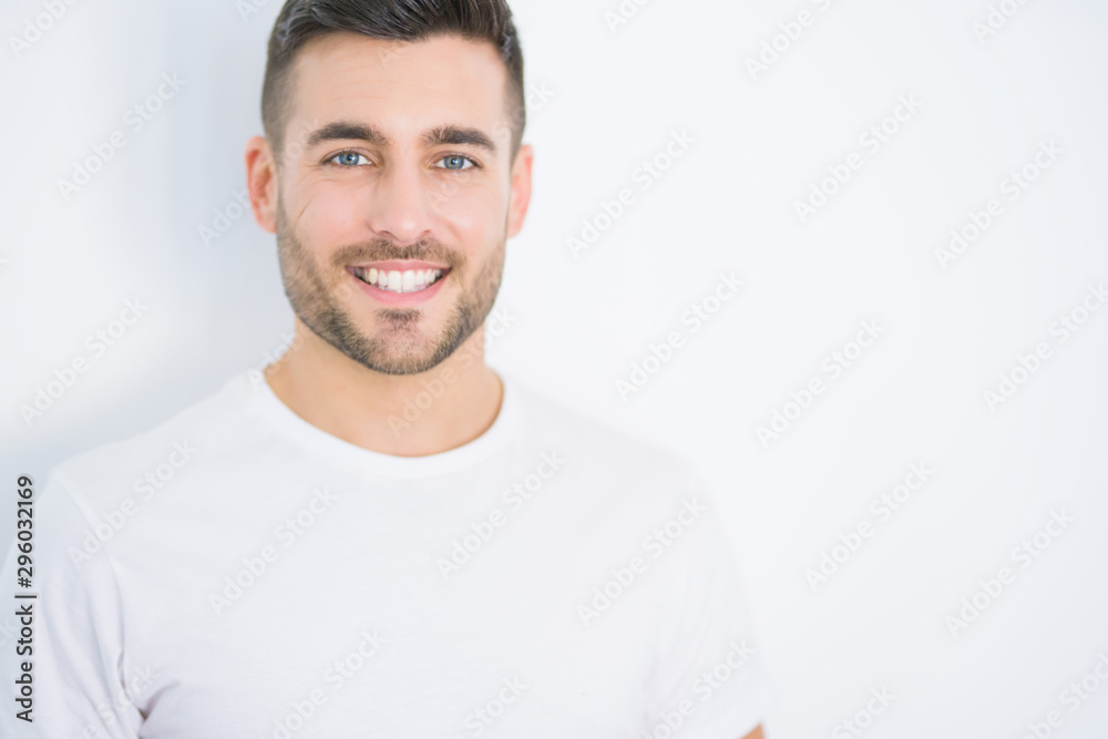 Fototapeta Young handsome man smiling happy wearing casual white t-shirt over white isolated background