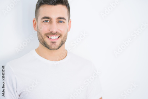 Stampa su Tela  Young handsome man smiling happy wearing casual white t-shirt over white isolate