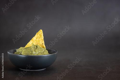 Fotografía  Green Guacamole with nachos in bowl on dark background