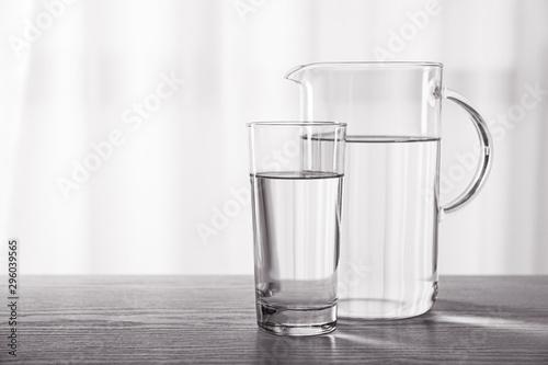 Fototapeta Glass and jug of fresh water on table indoors obraz