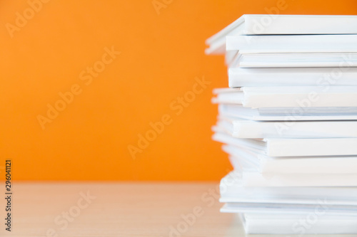 Fotografía  Stack of white books on colorful background.