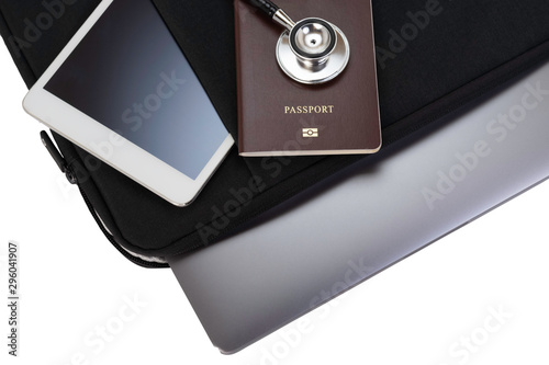 Valokuva  Computer notebook in black  bag ,white tablet pc, passport and medical stethoscope isolated on white background with clipping path