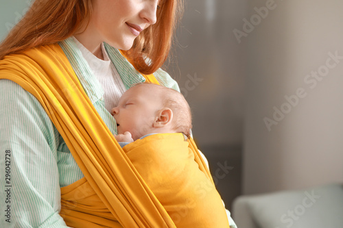 Fototapeta  Young mother with little baby in sling at home