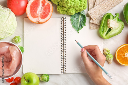 Woman writing something in notebook and healthy products on white table Obraz na płótnie