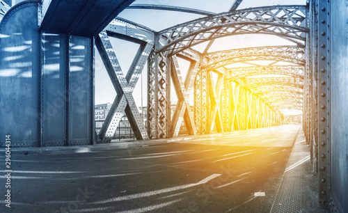 Spoed Fotobehang Bruggen Asphalt road under the steel construction of a bridge in the city on a sunny day. Evening urban scene with the sunbeam in the tunnel. City life, transport and traffic concept.