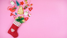 Festive Christmas Concept With Children's Stockings Filled With Cookies And Gifts On Pop Color Pink Background With Copy Space.