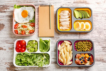Notebook With Healthy Food In Lunch Boxes On White Wooden Background. Diet Concept