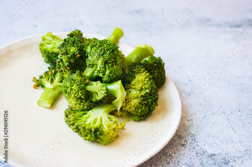 Photo Cooked or steamed broccoli inflorescence, sprouts on plate.
