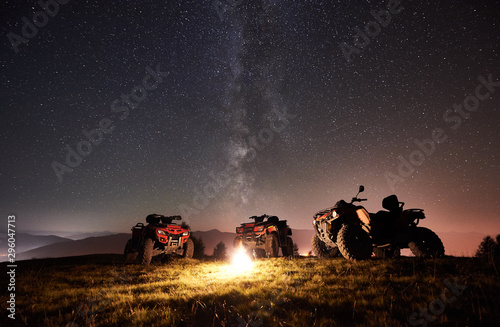 Marron chocolat Night picture. Three atv quad motorbikes standing on the top of mountain near burning bonpfire, under amazing night starry sky and Milky way on background