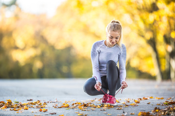 Woman runner tying shoelaces before jogging in autumn tree alley park. Sports female autumn outfit leggings and thermal underwear