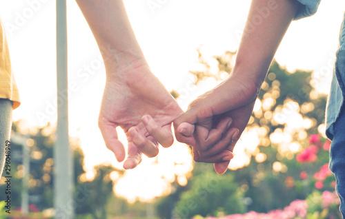 Obraz na plátně  Close up couple holding little finger with background sunset, vintage concept