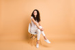 canvas print picture - Full length photo of amazing lady looking interested empty space sitting comfy chair good mood inspired wear casual clothes isolated beige pastel color background